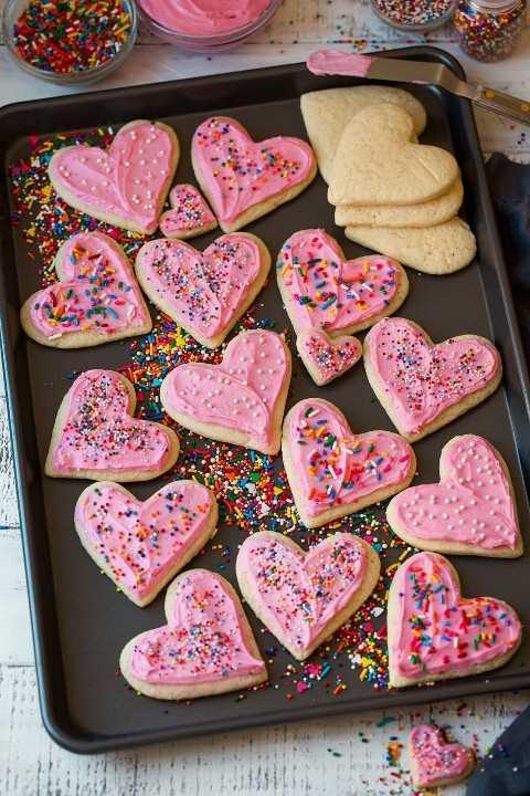 Recorte las galletas de azúcar en forma de corazón en una bandeja para hornear que se muestra esmerilada con chispas.
