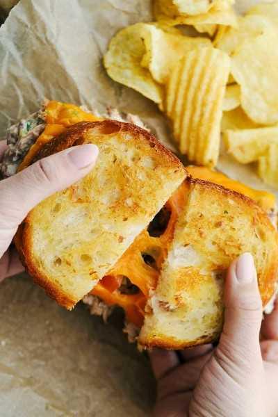Un sándwich de atún derretido se separó en una foto con patatas fritas en el lateral.