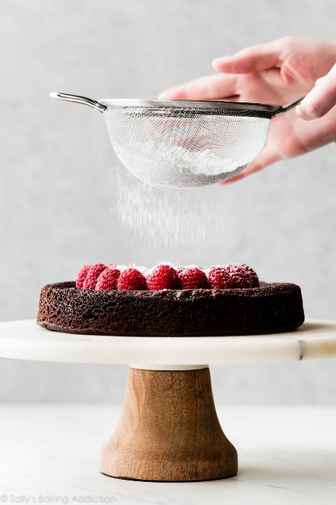 pastel de chocolate sin harina con frambuesas y azúcar en polvo