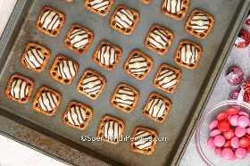 Pretzels cubiertos con abrazos de chocolate en una bandeja para hornear