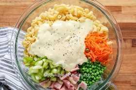 Ingredientes de ensalada de macarrones en un recipiente de vidrio antes de combinarlos.
