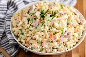 Un tazón lleno de cremosa ensalada de macarrones, adornado con cebollas verdes.