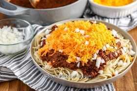 Espaguetis cubiertos con chile Cincinnati, cebolla picada y queso rallado.