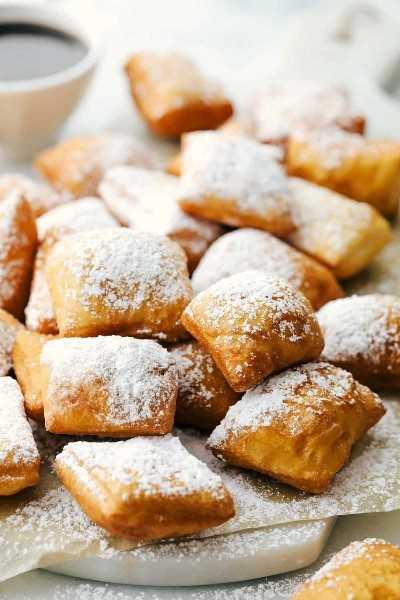 Varios beignets en una tabla de cortar espolvoreados con azúcar en polvo y jarabe de chocolate en el lateral.