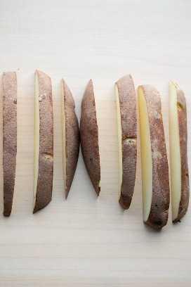 una patata pelirroja cortada en gajos