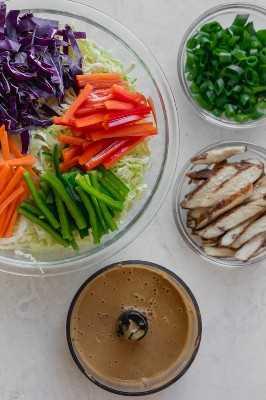 Col china picada, col roja, pimientos y zanahorias en un tazón grande. Al lado hay un tazón más pequeño de cebollas verdes y un tercer tazón de pollo en rodajas. Finalmente un pequeño procesador de alimentos con el aderezo de mantequilla de maní para la Ensalada Asiática de Pollo