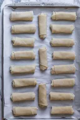 Bandeja de horno con papel pergamino que muestra los rollos de primavera de zaatar enrollados
