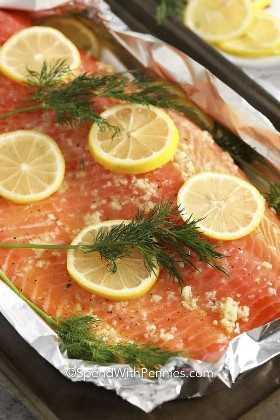 Filete de salmón crudo cubierto con mantequilla de ajo, rodajas de limón y eneldo.
