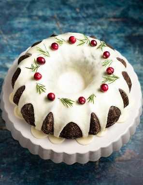 Bolo vegano de gengibre em uma banca de bolo, coberto com glacê, mirtilos frescos e raminhos de alecrim