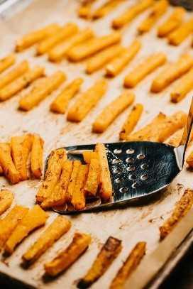 Uma espátula de metal que levanta as batatas fritas de abóbora assadas de uma assadeira.