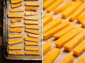 Batatas fritas de abóbora temperadas com tomilho e sal em uma assadeira antes de colocá-las no forno.