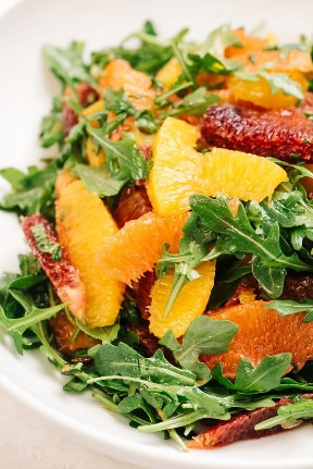 Side view, citrus salad with a variety of oranges with arugula and fresh mint.