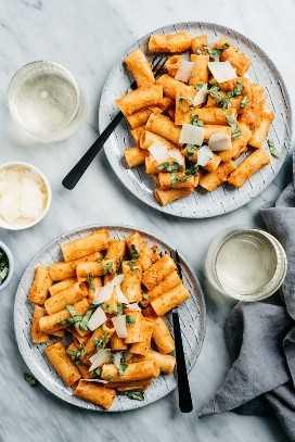 Dos platos de rigatoni con salsa cremosa de tomate sobre una mesa de mármol con vino blanco y un pequeño tazón de queso parmesano.