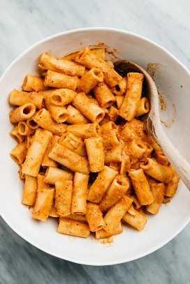 Pasta rigatoni cocida mezclada con salsa de crema de tomate en un tazón blanco grande.