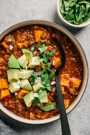 Un plato de carne de res y batata chile entero30 sobre un fondo de cemento con una sopa negra pronto.