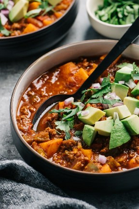Vista lateral, chile entero30 adornado con aguacate, cebolla roja y cilantro.