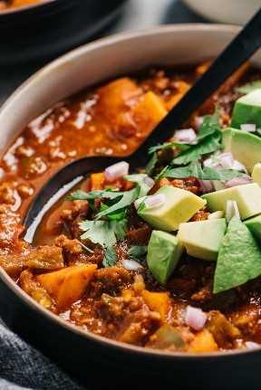 Vista lateral, un tazón de chile de carne saludable con camote y verduras adicionales.