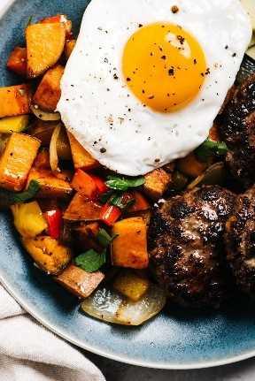 Desde arriba, un plato de desayuno entero con hash de camote, salchichas y un huevo frito.