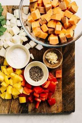 Los ingredientes para el picadillo de batata picados y mostrados en una tabla de cortar.