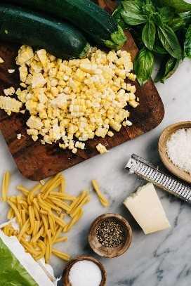 Vista aérea de todos los ingredientes para la pasta de verano con calabacín y maíz dulce dispuestos sobre una mesa de mármol.