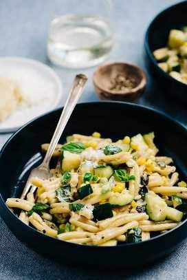 Vista lateral de un plato de pasta de verano con calabacín y maíz dulce sobre un mantel azul.