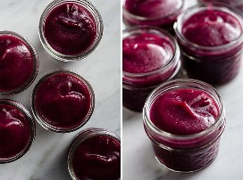 Mild apple-blueberry sauce infused with vanilla in small glass jars.