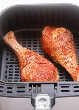 Pernas de peru temperado cru em uma cesta de fritadeira