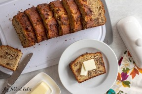banana bread slices with nuts on a cutting board with a slice on a small plate with butter