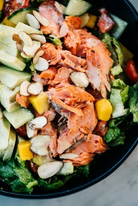 From above, a detailed view of salmon and avocado on vegetable salad with creamy lemon dressing.