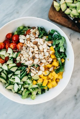 The base for the salmon and avocado salad in a large white salad bowl: romaine lettuce, cherry tomatoes, English cucumber, champagne mangoes and sliced almonds.