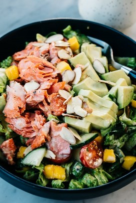 From above, a bowl of salmon salad with avocado, mango, and creamy lemon dressing.
