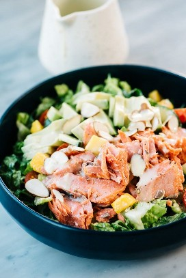 Side view, salmon and avocado salad in a blue bowl with a small jar of lemon dressing on the side.