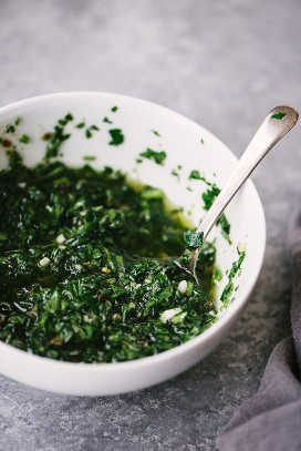 Italian salsa verde verde sauce in a white bowl with a spoon on a cement background.