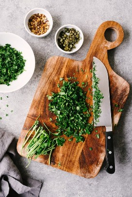 How to make Italian green sauce. Flat-leaf parsley is chopped on a wooden cutting board with small bowls of capers and red pepper flakes.