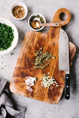 How to make Italian green sauce. Capers and garlic are minced on a wooden cutting board with a bowl of chopped parsley on the side.