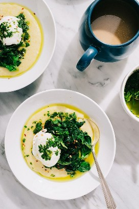 Two bowls of polenta topped with sautéed spinach and a poached egg, drizzled with Italian green sauce.
