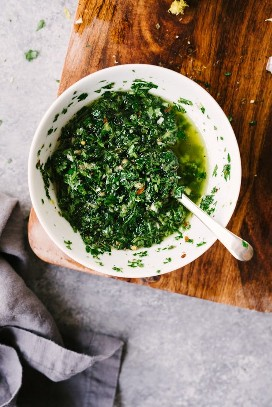 A small white bowl filled with freshly prepared Italian green sauce on a wooden cutting board with a gray linen napkin.