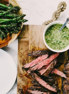 Slices of medium rare grilled steak on a cutting board with a small bowl of Italian green sauce and a large bowl of grilled asparagus on the side.