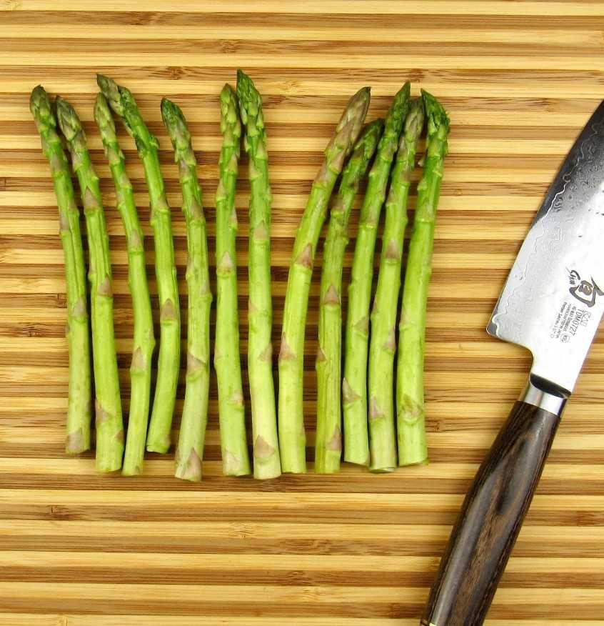 corte os aspargos na tábua com uma faca