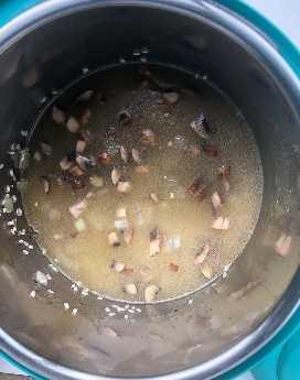 caldo de galinha e arroz e cogumelos em uma panela instantânea