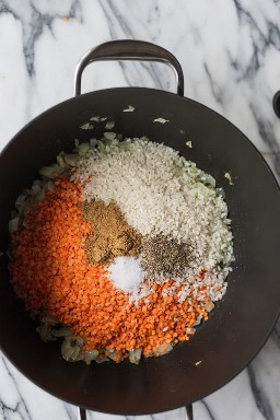 Panela grande com cebola, lentilhas, arroz, cominho, sal e pimenta para fazer sopa de lentilha esmagada