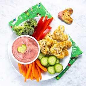 tazón de hummus de remolacha con plato lleno de verduras picadas y pan de pita de corazón cortado.