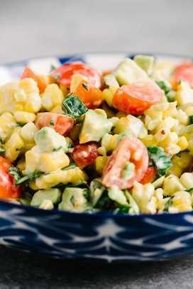 Detalle de la vista lateral de ensalada de maíz y tomate a la parrilla con aguacate, albahaca y aderezo cremoso de suero de leche.