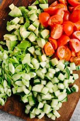 Vista aérea de aguacate cortado en cubitos, pepino, tomate y rodajas de cebolla verde en una tabla para cortar.