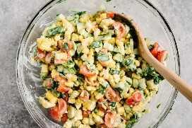 Arriba, ensalada de tomate y maíz con aderezo de suero de leche en un tazón de vidrio con una cuchara de madera.