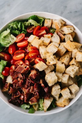 From above, a white salad bowl filled with the ingredients for a BLT salad: chopped lettuce, grape tomatoes, bacon, and sourdough croutons.