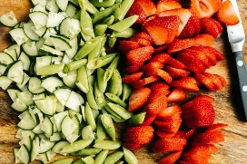 Chopped cucumbers, peas, and sliced ​​strawberries on a cutting board.