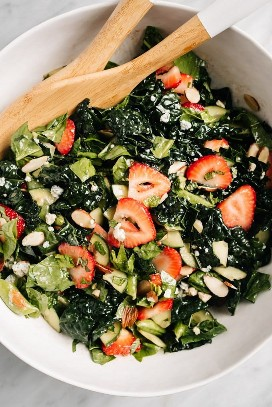 A large white bowl filled with strawberry kale salad and wooden spoons.