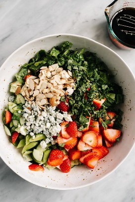 The ingredients for the strawberry kale salad in a large bowl from above.