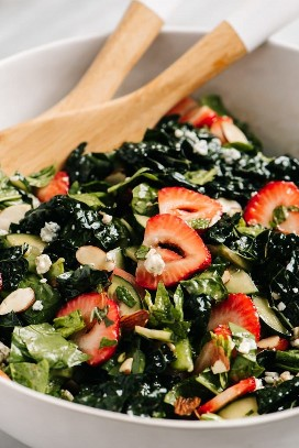 Strawberry kale salad with balsamic vinaigrette in a white bowl with wooden spoons.